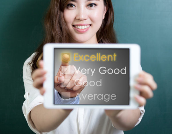 "Female holds up device with options displaying ""Excellent, Very good, Good, and Average,"" while finger points to ""Excellent"""