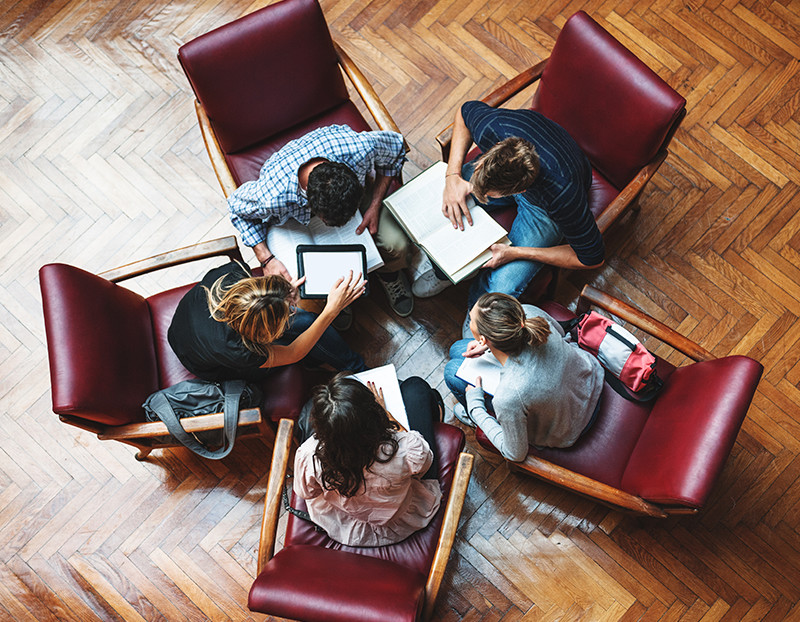 Students bring chairs together in circle and collaborate over papers, computers, and books