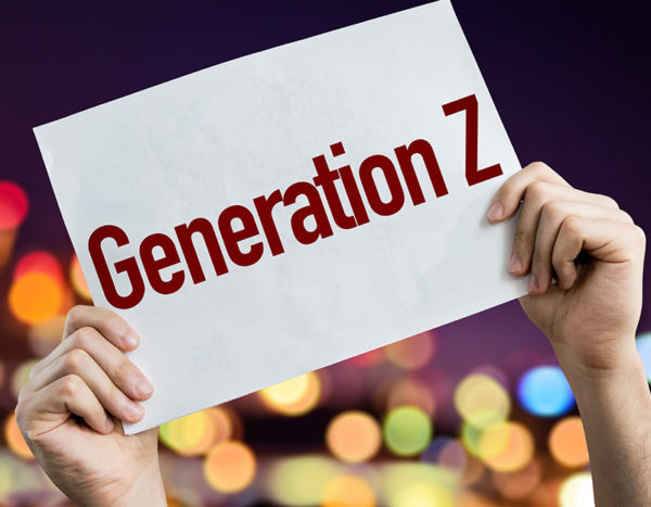 "Hands hold up sign that says ""Generation Z"" with blurred lights in the background"