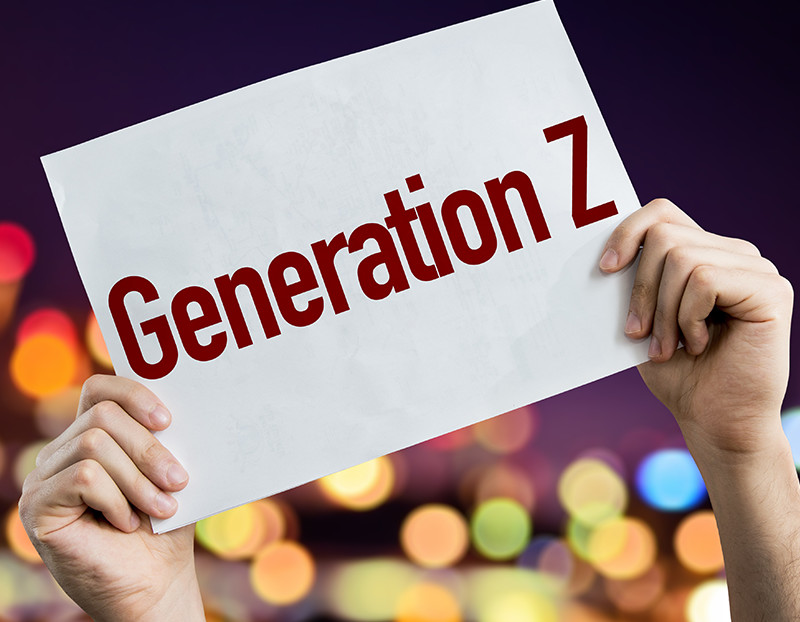 """Hands hold up sign that says """"Generation Z"""" with blurred lights in the background"""