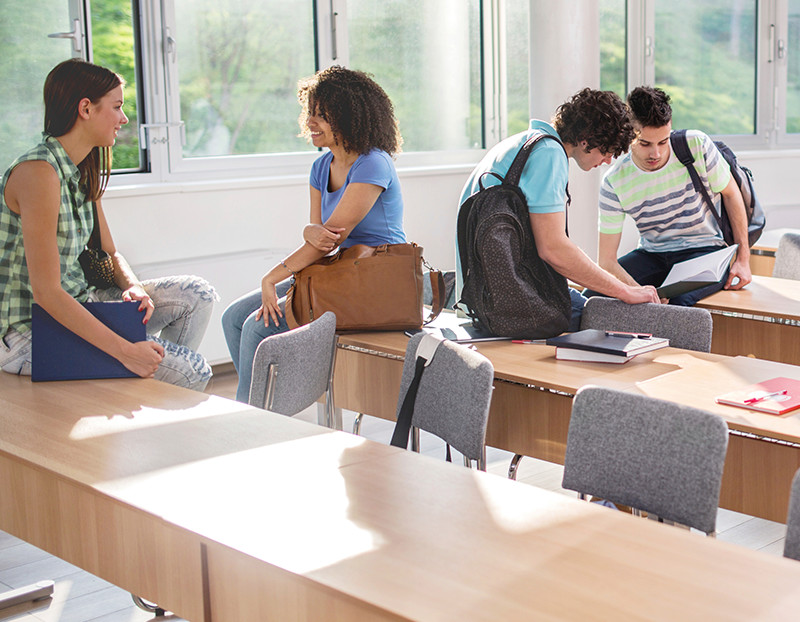 Students talk amongst each other sitting casually on desks and chairs before class starts