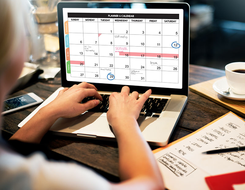 Person types on computer displaying intricate and planned calendar full of events