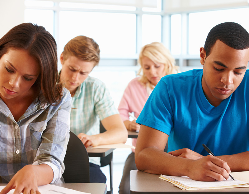 Four students sit in desks and concentrate on taking exam