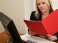 Woman looks at file folder with laptop in front of her