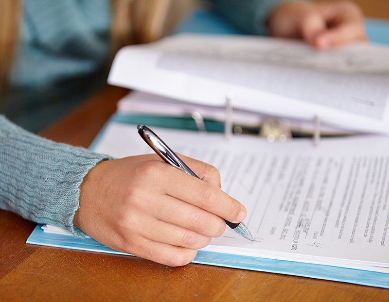 Person holds pen and writes notes on binder paper