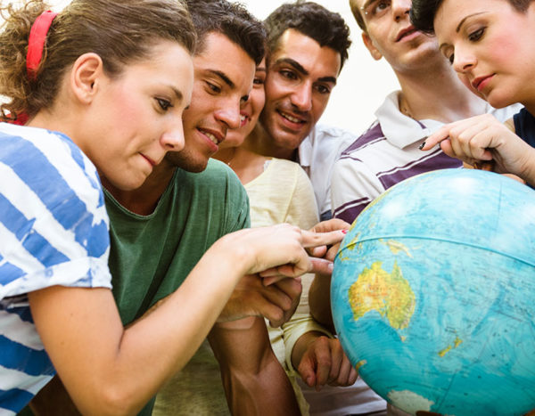Students point to different places on a globe