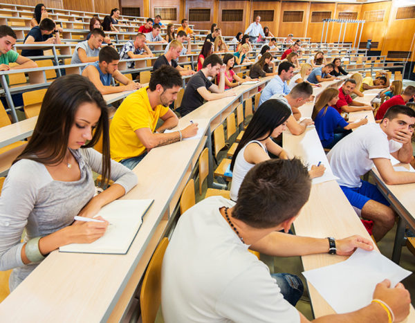 Large class lecture features numerous students taking exam