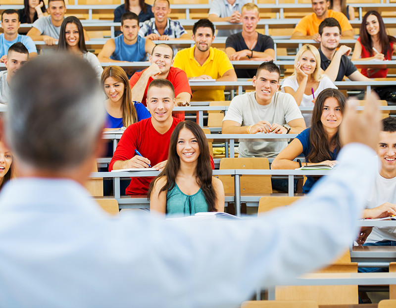 Instructor teaches class in front of large lecture hall full of students