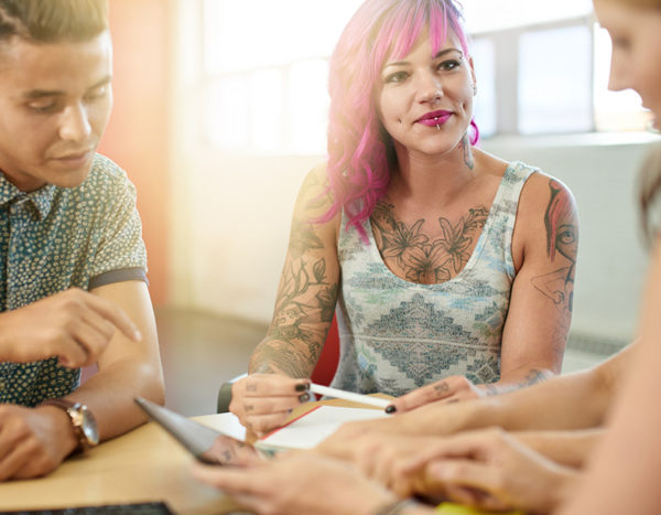 Female with tattoos sits at table with others and listens to them talk