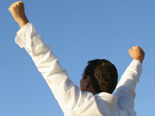Person holds up hands in the air of success with sky in the background