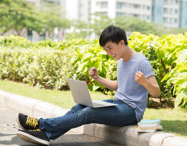 Student celebrates while looking at computer screen sitting outside on campus