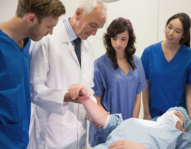 Doctor checks patient's pulse while students observe