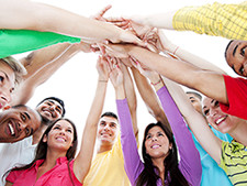 Individuals all put their hands together in group huddle