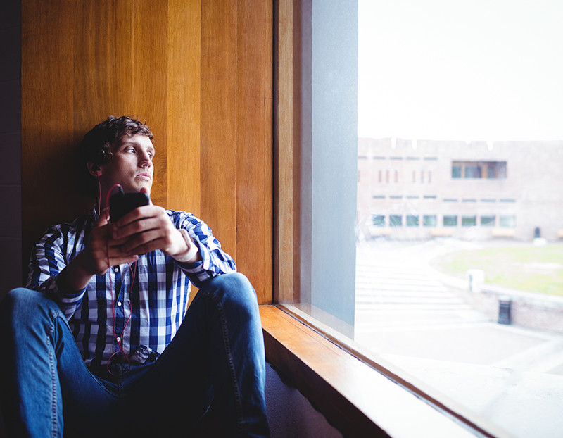 Student looks outside window on campus with cellphone in hand