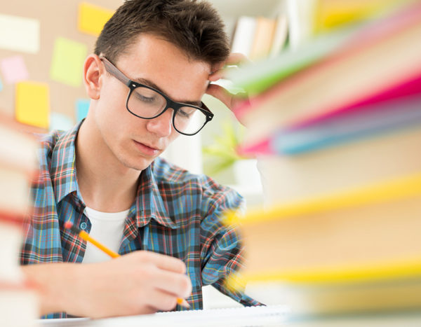 Student concentrates on assignment with books, stickies and papers blurred around them