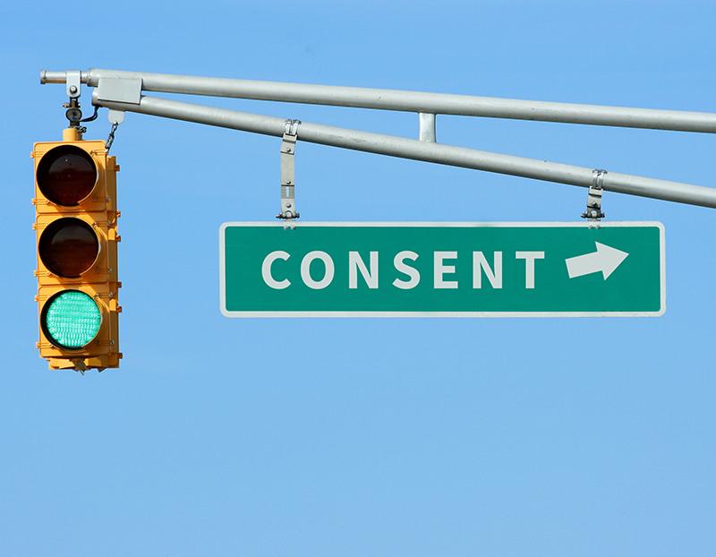 "Green street signs reads ""Consent' next to green traffic light"