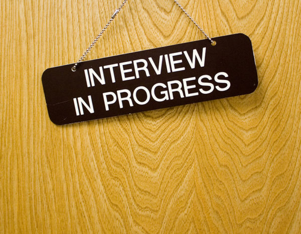 "A sign with the words, ""Interview in Progress"" hangs on door"