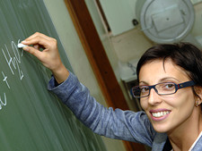 Teacher smiles at camera while writing on chalkboard