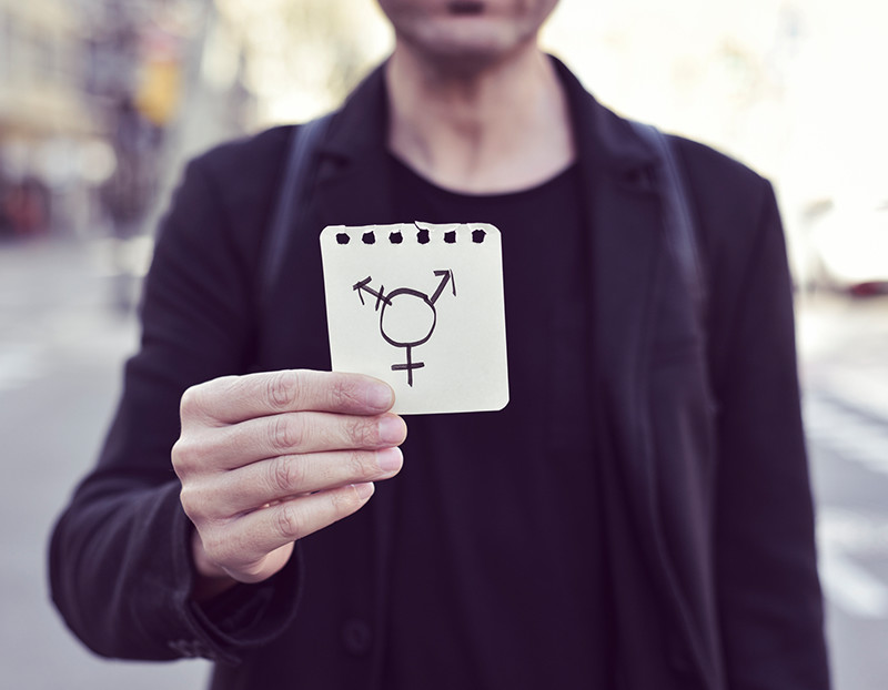 Person holds up notepad with transgender sign drawn on it