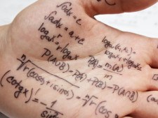 Hand has formulas written on it to use for upcoming exam