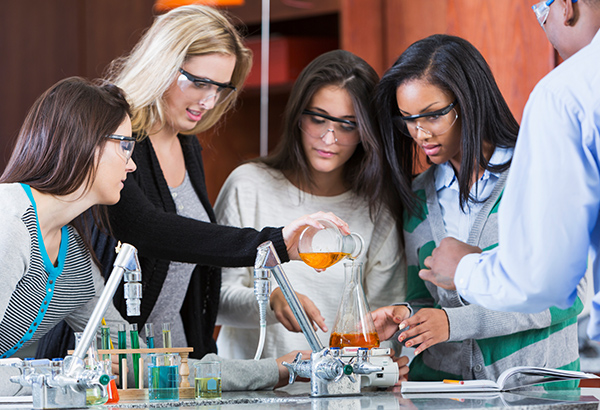 Group of students use beakers in science course to execute lab