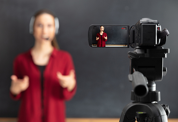 Video camera records person talking in front of chalkboard