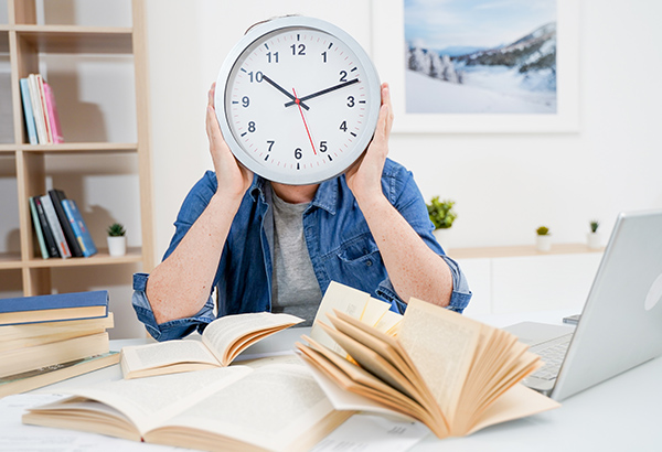 Person holds up clock in replace of their head with books and computer laid out in front of them