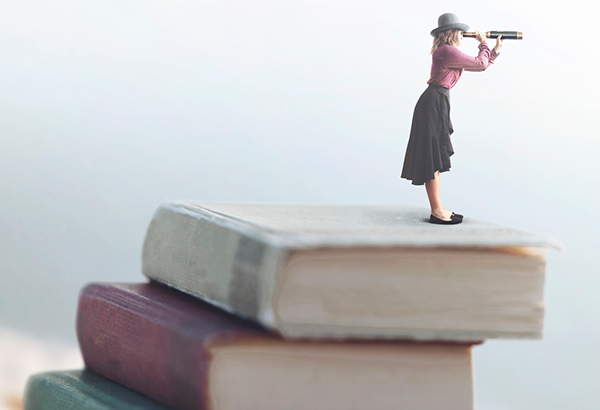 woman with telescope looking on top of books