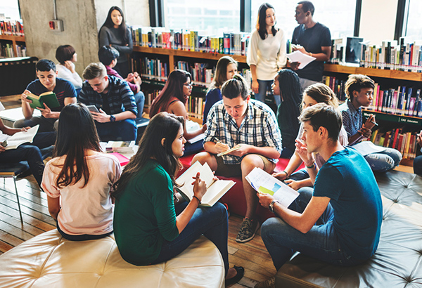 group-of-students-actively-talking-in-circle-with-books