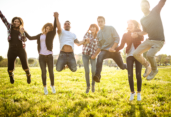 group-of-students-jumping-outside-grass-sunshine